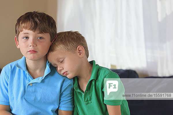 Boys with hearing impairments sitting on their couch