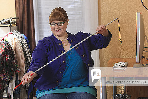 Woman who is legally blind preparing her cane to use in her house