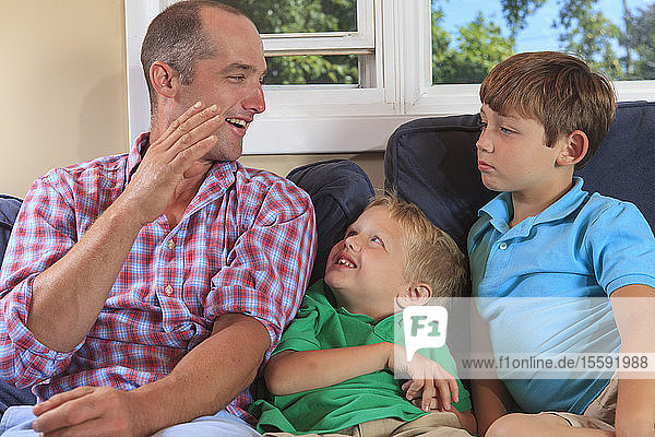 Father and sons with hearing impairments signing 'B' in American sign language on their couch