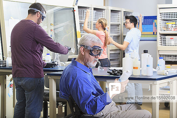 Engineering professor with muscular dystrophy looking at chemical reagent along with students in a chemical laboratory