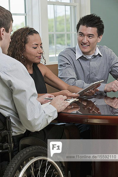 Visually impaired Hispanic businesswoman discussing with two businessmen in an office