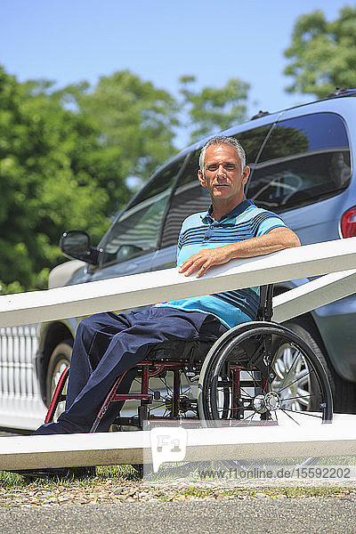 Man with a Spinal Cord Injury in wheelchair in front of his accessible car