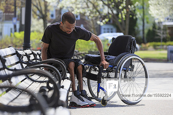 Man who had Spinal Meningitis getting out of a park bench and into his wheelchair