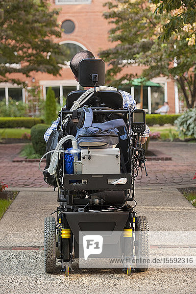 Rear view of a man with Duchenne muscular dystrophy in a motorized wheelchair on the street