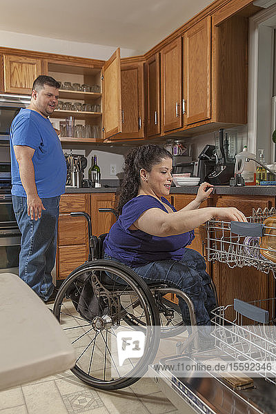 Woman with Spina Bifida and her husband using the dishwasher in kitchen