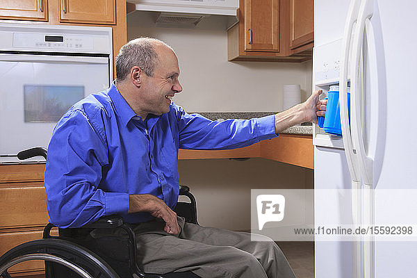 Man with Friedreich's Ataxia and deformed hands using the water dispenser in his refrigerator