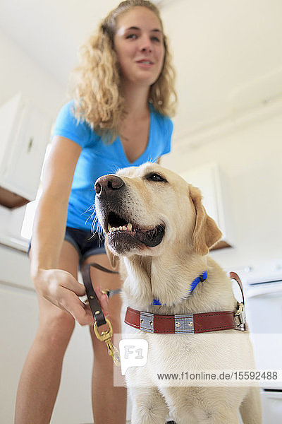 Woman with visual impairment hooking the leash on her service dog