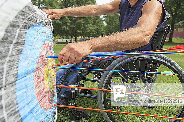 Man with spinal cord injury in wheelchair removing arrows from target after archery practice