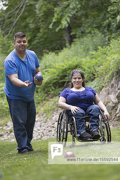 Woman with Spina Bifida in a wheelchair playing bocce ball with her husband