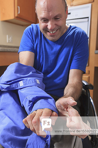 Man with Friedreich's Ataxia and deformed hands removing his Velcro shirt