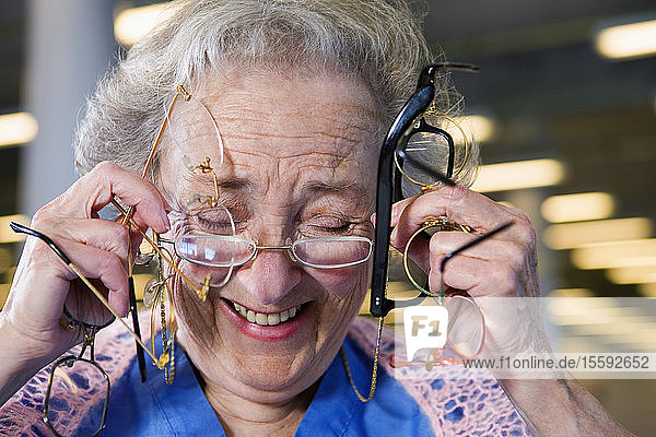 View of a cheerful senior woman holding glasses