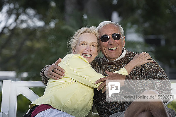 Portrait of a senior couple smiling in a park.