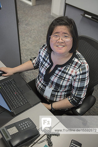 Asian woman with a Learning Disability working at her computer in office