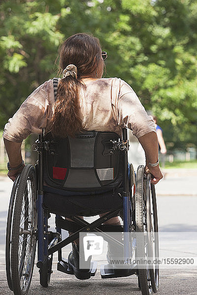 Woman with spinal cord injury crossing street at accessible access