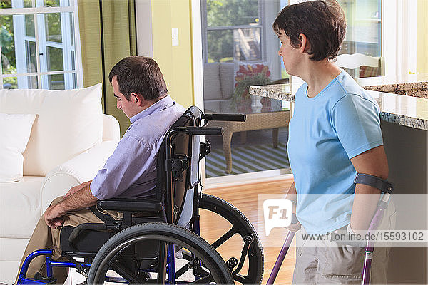 Wife looking at husband in their home both with Cerebral Palsy