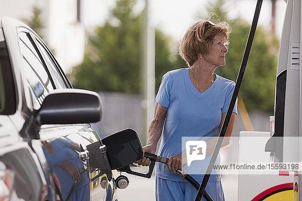 Woman filling car at a gas station