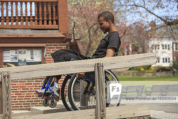 Man in a wheelchair who had Spinal Meningitis using a public building ramp