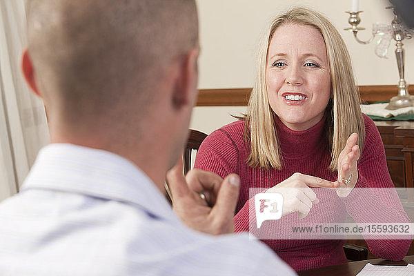 Frau  die das Wort Afford in amerikanischer Zeichensprache gebärdet  während sie mit einem Mann kommuniziert