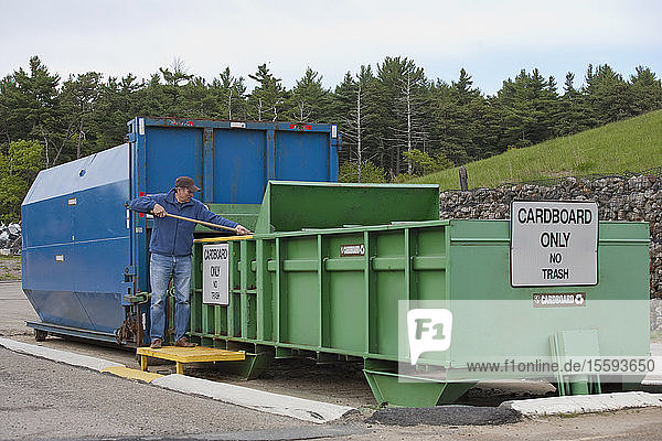 Engineer arranging cardboard at Cardboard Only recycling compactor connected to container