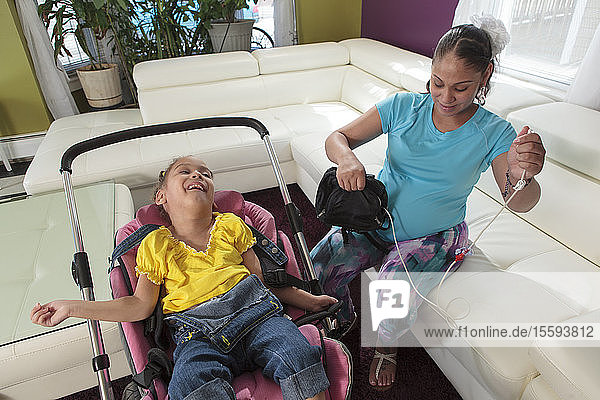 Mother preparing feeding tube for small daughter with Cerebral Palsy