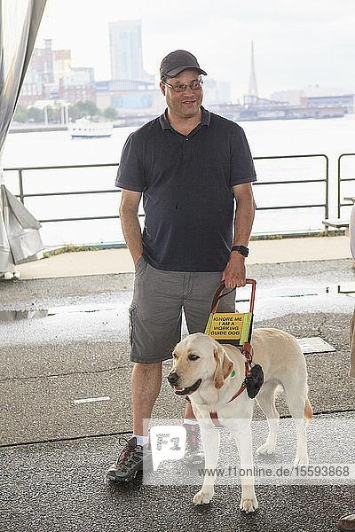 Mann mit Sehbehinderung und sein Diensthund