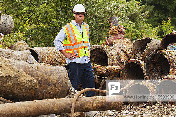 Engineer with old water pipes removed from city piping underground