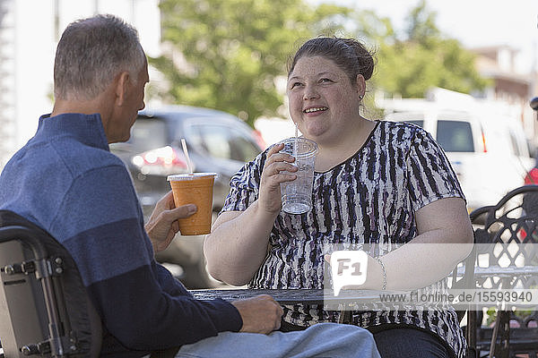 Woman with Visual Impairment sitting at a café with her father