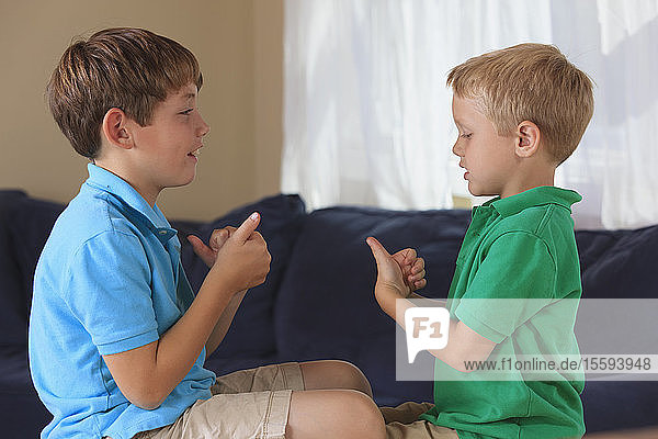 Boys with hearing impairments signing 'sports' in American sign language on their couch