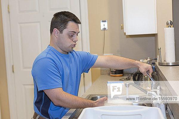Man with Down Syndrome washing dishes in the kitchen