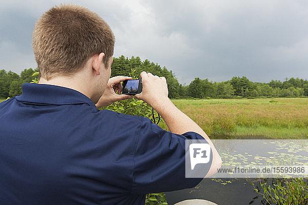 Public works engineer photographing swamp near reservoir
