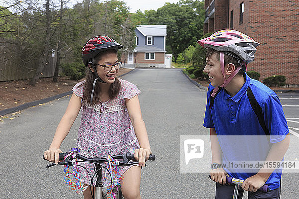 Teens girl who has Learning Disability riding bicycle with her brother