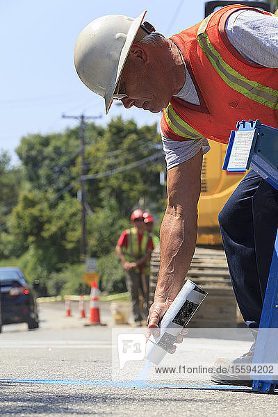 Construction supervisor marking alignment of water main on pavement