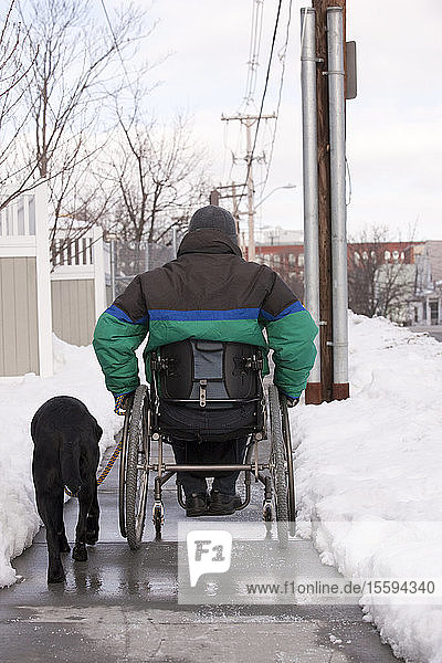 Woman with multiple sclerosis in a wheelchair with a service dog on a snowy street