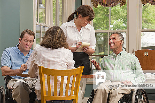 Two men in wheelchairs with Spinal Cord Injuries and a friend ordering food in a café