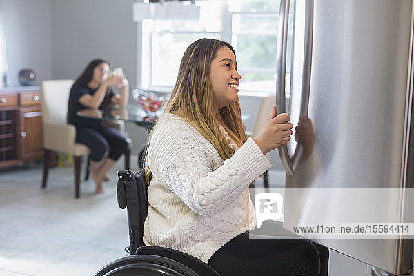 Woman with Spinal Cord Injury opening refrigerator