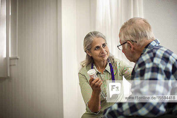 Female doctor listening to an elderly male patient while holding a bottle of medication