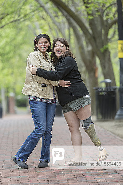 Two happy young female friends hugging  one with a prosthetic leg