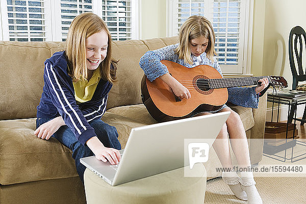 View of two sisters sitting on sofa with a laptop and a guitar.