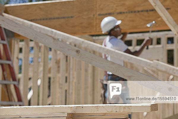 Carpenter hammering beam on house framing