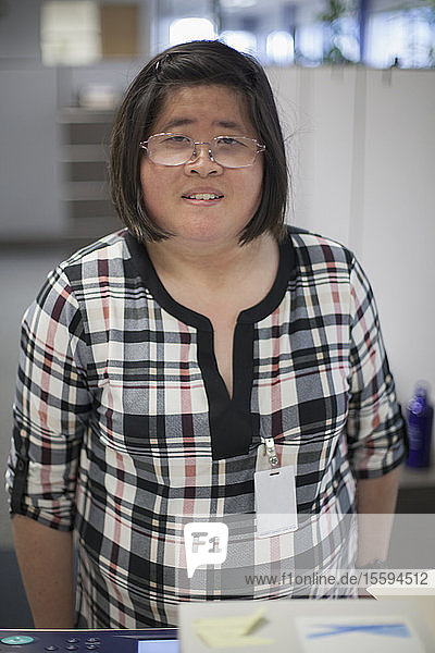 Asian woman with a Learning Disability working at a copy machine