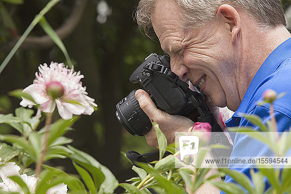 Man with Cerebral Palsy and dyslexia photographing his flowers