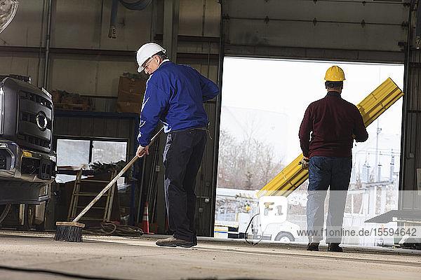 Maintenance supervisor cleaning utility garage one man carrying hole shielding