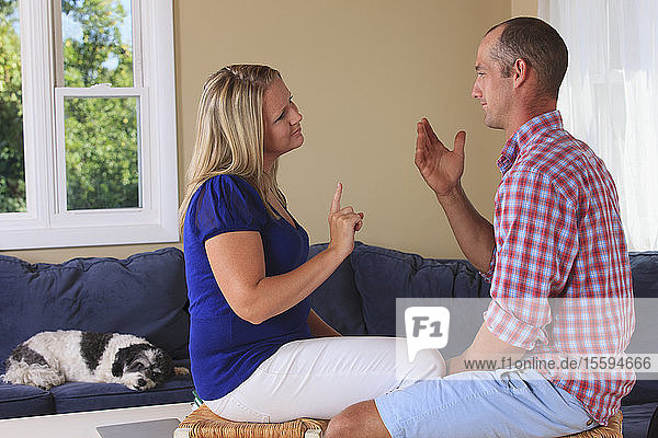 Husband and wife with hearing impairments signing 'where' in American sign language