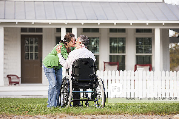 Couple kissing in front of their new home while he is in a wheelchair