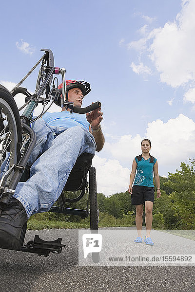Young man with a Spinal Cord Injury riding adaptive bike with a young woman standing in the background