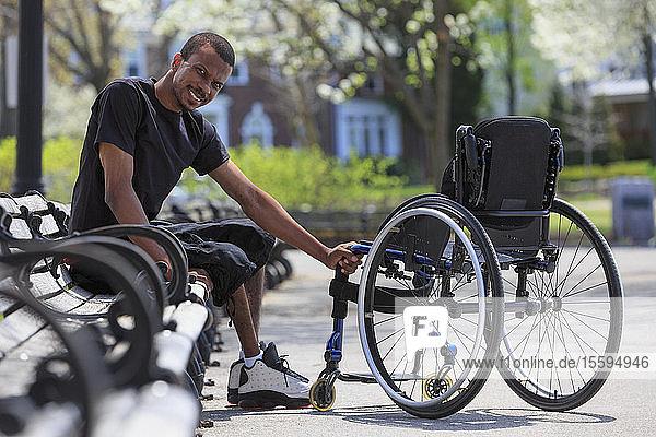 Man who had Spinal Meningitis sitting on a park bench near his wheelchair