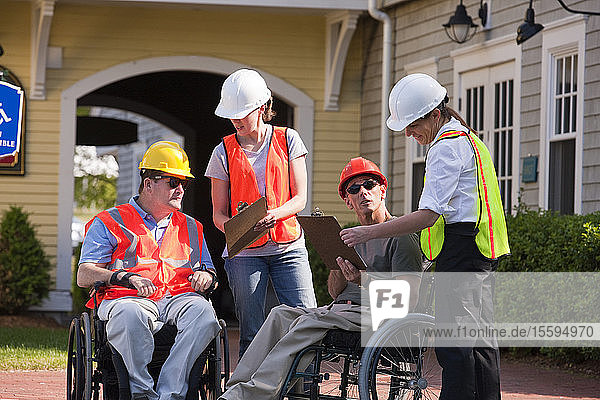 Project engineers discussing data at new building site  two with Spinal Cord Injuries