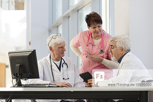 Doctor with muscular dystrophy in wheelchair in discussion with a doctor and nurse