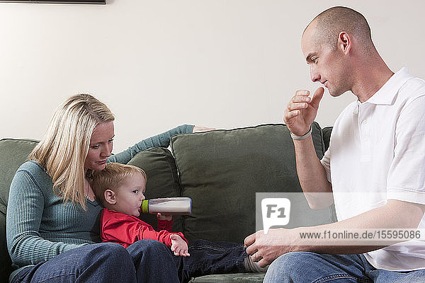 Man signing the word 'Drink' in American Sign Language while his son drinking milk