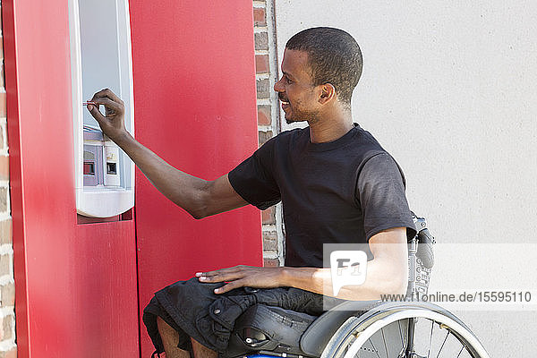 Man who had Spinal Meningitis in a wheelchair at a bank ATM